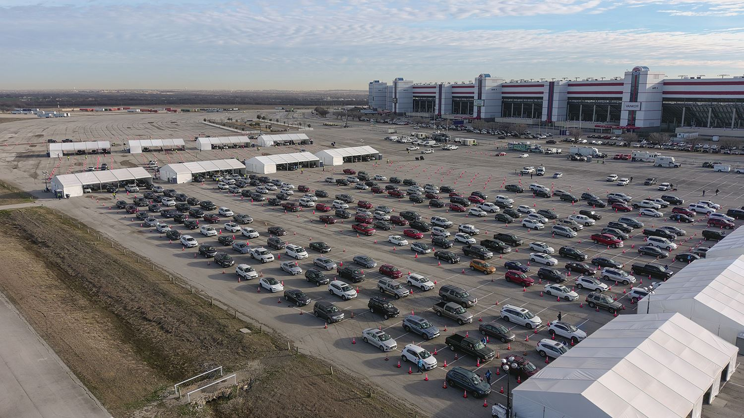 An overhead photo shows lines at the Texas Motor Speedway vaccination clinic.